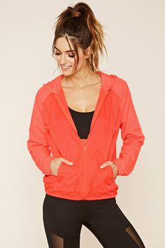 A woven windbreaker jacket with a zippered front, a toggled drawstring hood, long sleeves, split kangaroo pockets, and an elasticized hem and cuffs.