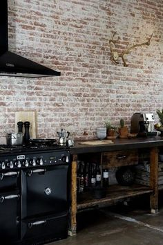Loft kitchen with distressed brick walls and vintage inspired black appliances