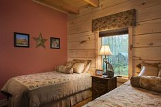 Spare bedroom with exposed timber ceiling and solid log exterior walls with a lovely shade of red on the interior wall.