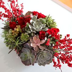 Rich in color and texture, succulents add stylish impact to holiday centerpieces. Besides their beauty, one of the biggest advantages of succulents is that they are so hearty, and will stay looking fresh throughout the season. In fact, when you are through with the centerpiece, you can even replant the individual blooms. Accented with red roses and...