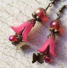 Beautiful fucia pink lucite fantasy earrings. It is made of fire polished czech AB crystal and glass beads with antiqued brass findings. The lucite flowers give a subtle and soft look. Then a butterfly charm completes the delicate design. Perfect with a spring outfit. Shipping calculated at checkout.