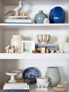 Boho-Chic Design: eclectic, modern, and vintage by Emily Henderson. A collection of beautiful things is styled with balance and contrast. The white and blue vases and objects feel collected over time and the composition is not symmetrical, yet completely balanced. Stacks of books ground each shelf, but by staggering them it creates visual balance.