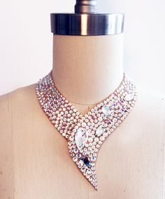 Simplistic swirl collar necklace complete with Swarovski Crystal and Crystal AB rhinestones, offset with several pear shaped sew on jewels.
