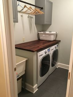 Modern laundry room with gray cabinets and a butcher block folding table.