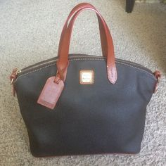 """Authentic Brown Dooney & Bourke purse. Authentic Brown Dooney & Bourke purse.  Red inside. Comes with brown strap for the option of wearing the purse on shoulder.                                                                     • L 11.75""""   W 7.25""""   H 10.25"""" • One inside zip pocket • Two inside pockets • Cell phone pocket • Inside key hook • Handle drop length: 4.75"""" • Strap drop length: 12.50"""" Dooney & Bourke Bags"""
