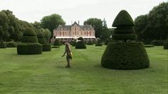"""The groundskeepers painted brown patches in the grass green before the party. One says, """"Don't tell Mr. Valentino. He doesn't know we're doing this.""""chateau-painting grass"""