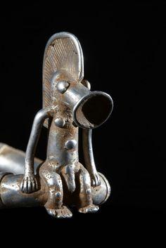 """Ces chevillères font partie des éléments de parure qui pouvaient être conseillés par le devin (Sando). On les définit parfois aussi comme chevillières en """"pont de bateau""""en raisonde leur forme. Cette splendide pièce est un objet de prestige en témoigne la richesse de l'ornementation. La matière choisie est l'alumunium massif, ce qui est bien moins courant que les bronzes, mais plus léger à porter."""