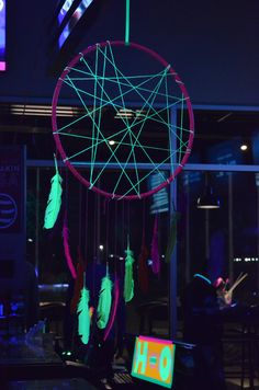 Black light neon dream catcher made with a hula hoop, neon yellow yarn and feathers.