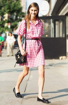 A pink and white gingham shirtdress is worn with a black belt, shoulder bag, and loafers