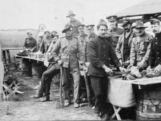 Meal Time Several soldiers, wearing a variety of uniforms, are involved in food preparation at an army transit camp in the Winchester area during the First World War.   WINCM:PWCM 29557