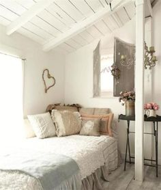 Small bedroom painted all in white with slanted roof