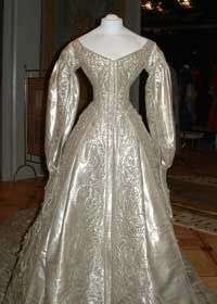 Catherine the Great of Russia's wedding gown.  Wedding dress was made of Silver brocade.  The gown shimmered.  There are glittered hand embroidered roses all over the dress.  She wore a cloak of silver lace over the dress so heavy she could barely move.  It was all quite uncomfortable.  Especially after the crown was added.  She had a terrible head ache after the 3 hour ceremony and hours of activities to follow.