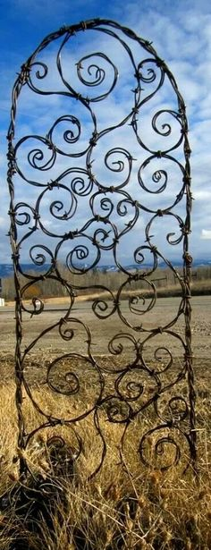 How cool is this garden art?! Barbed wire! Maybe an arch like this with roses or real flowers for behind the bridal table.