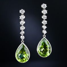 Peridot and Diamond Drop Earrings. These 1 and 1/2 long dangles glisten with a gorgeous pair of bezel-set Jolly Rancher green pear shape peridots. The beautiful gemstones, which together weigh 11.00 carats, swing and sway below a sparkling row of round brilliant-cut diamonds. All set in bright and gleaming platinum.