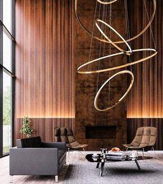 Uma luminária escultural num ambiente igualmente maravilhoso. O painel de madeira que cobre toda a parede principal tem um detalhe que esconde a iluminação de led.