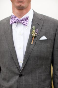 This groom looks perfect with his purple bow tie and boutineer
