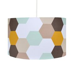 A handmade lamp shade with geometric hexagon design, soft muted colours in shades of grey, blue, brown and mustard yellow make for a very contemporary design.