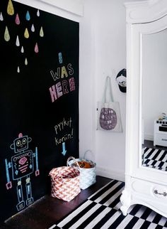 Ally's room or playroom: This chalkboard wall helps make a graphic statement in this girl's room. it's especially successful with bright chalk drawings and a graphic striped rug.