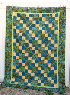 Here's a four-patch quilt in blues, greens and neutral Batik tones. See my entire quilt collection at www.etsy.com/shop/Quiltquility #Quiltquility