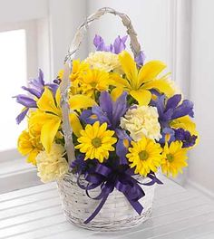 FTD Spirit of Spring Basket - PREMIUM  Price: 57.90    Capture the Spirit of Spring with this traditional bouquet. A handled bamboo basket holds bold purple iris and statice that defer to lemon yellow Asiatic lilies, soft yellow carnations and bright yellow daisy poms. It's the perfect petite basket to celebrate any occasion.