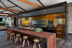 Contemporary kitchen with a variety of metal finishes is nicely offset by the rustic wood dining bar in this converted warehouse in Sydney Australia. [1700  1131]