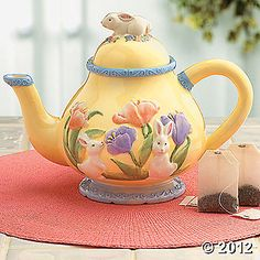Easter Teapot. Topped by a bunny on a flowerbed, then bordered with more bunnies and blooms, this ceramic pot is perfect for a springtime tea.