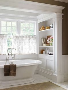 Love the stand alone tub in the window light w/built in, and wainscotting. Needs a chandelier above the bathtub.