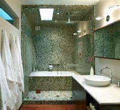 une mosaïque verte et une paroi en verre dans la petite salle de bains