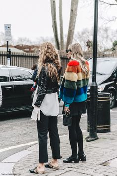 Street Style_The Best of Friends: cropped leather jacket/long line shirt/cropped pants worn with Gucci slides. Coloured faux fur jacket worn with a-line mini skirt. AW16 street shot | Saved by Gabby Fincham |