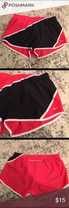 "Nike running shorts magenta/ black Sz M Nike dri-fit shorts in magenta and black with white trim. Adjustable ties inside waistband. Pocket with zipper that would fit keys and money, reflective strip above pocket. Another small pocket inside shorts, attached undies. Waist is 31"" leg opening is 26"" around. Nike Shorts"