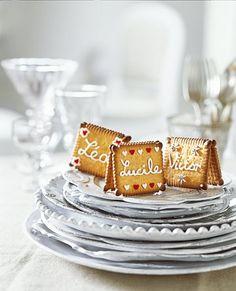 Des marque-place en petits beurres collés par deux et décorés de glaçage et de cœurs en sucre