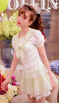 A classic sailor Japanese school girl style blouse in white and lime green gingham. The blouse has a large sailor collar and short sleeves that fasten with a shimmering green pearl. In the centre is a large detachable matching bow. The shirt is finished with lace hem and shimmering lime greem pearls.