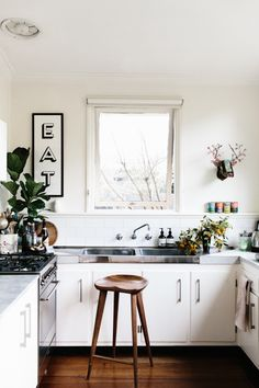 white walls, stool, white cabinetry