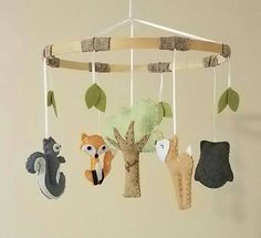A natural handmade mobile with a fox, deer, squirrel and owl for a nature woodland forest animal theme baby room.