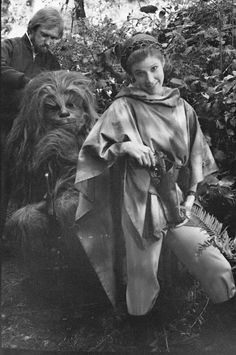 Carrie Fisher poses on location while Peter Mayhew in full Chewie mode watches on - Return of the Jedi