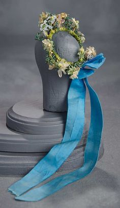 """The wire-framed coronet has a bounteous arrangement of flowers, beads, and tiny berries formed from tiny glass beads. Blue silk streamers cascade from the coronet. 2 1/2"""" diam. Circa 1870."""