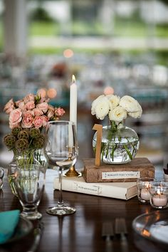 Eclectic table decor with pink and white flowers and vintage books - photo by Elizabeth Lloyd and Dave Getzschman | via junebugweddings.com
