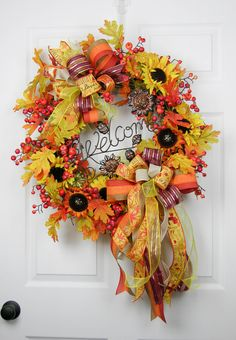 Fall colors abound in this grapevine wreath with all the colors of the season. It is filled with orange and yellow sunflowers, turning fall leaves, orange persimmon berries, and pumpkins. A bronzed me
