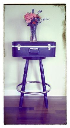 1repurposed hard-sided suitcase. 1swivelling barstool. Black paint. Flowers. Remove barstool seat.  Measure distance between holes in barstool, mark on suitcase. Drill small holes in suitcase Screw suitcase to stool Paint. Love.   Side Table, Occasional Table, Repurposed Suitcase, DIY, Accent Furniture