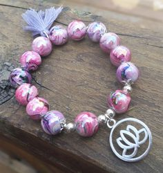Feminine and flirty pink and purple swirled acrylic beads with silver tone bead caps and accents. - Silver tone Lotus flower charm. - 6.5 Inches un-stretched (approximately). This bracelet best fits people with a medium frame. - Ships from Canada.  Lotus flowers are symbols of strength, purity, and beauty, as they thrive even in the murkiest of waters. The shiny, high-quality acrylic b...
