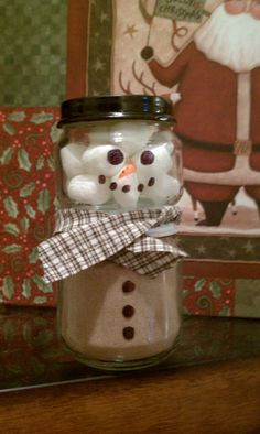 Snowman made from a baby food jar. The top jar is filled with marshmallows. The bottom jar is filled with hot chocolate mix.