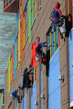 Lucrătorii de la o firmă de curățare a ferestrelor s-au îmbracat în costume de super-eroi pentru a înveseli pacienții unui spital pentru copii.