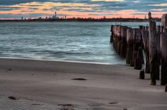 While the Manhattan skyline is visible in the distance, the beaches of Rockaway Beach seem a world away.   rockaway, rockaway beach, rockaway ny, rockaway new york, nyc, ny, new york city, queens, brooklyn, bridges, sunset,sunsets,beach, beaches,sunrise,sunrises, piling, pilings, dock,docks, jamaica bay ny, marine park, parks, atlantic, east coast, the rockaways, night, nights, light, lights, nighttime,moonlight,moonlit, welcome to the rockaways,a long way from manhattan