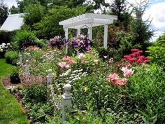 Lilies, Shasta daisies, roses and many other flower surround a peaceful arbor. From Cottage Gardens We Love