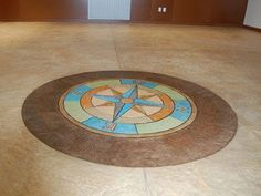Compass rose medallion stamped onto a concrete floor at SkyView Academy. The medallion was stained the school colors.