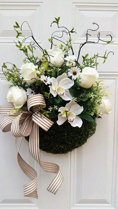 This beautiful Moss Covered Basket filled with white roses and orchids is the perfect Spring Door Décor for your home. Simple and elegant. It is approx. 24 from top of willow branches to bottom of basket and approx. 18 wide. Use it on your door or as part of your indoor décor. You