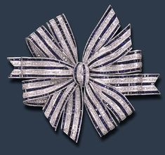 A DIAMOND AND SAPPHIRE BOW BROOCH   The ribbon bow alternately-set with calibré-cut sapphire and circular-cut diamond lines, mounted in platinum  The total weight of the sapphires and diamonds is approximately 30.00 and 3.50 carats