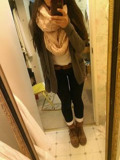 Short lace up boots, long socks, black pants, scarf, green oversized cardigan, and neutral colored top.