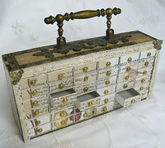 cigar box turned into a cabinet with tiny drawers by using matchboxes!  This is so sweet, and I love all the details...the paper, lace, brass corners and that cabinet pull for a handle finishes it off perfectly!