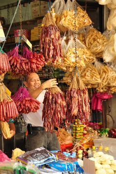 Chowrasta Market in the centre of George Town ~hanging up chinese dried pork sausages (lap cheong) at a sundry shop